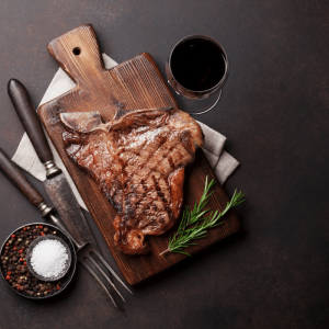 t-bone steak on table with wine cutlery and herbs